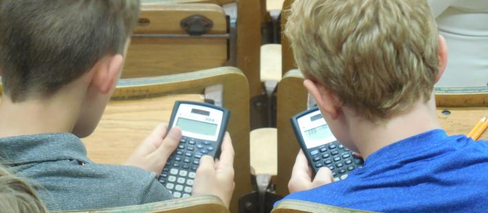 2 kid checking out their calculators